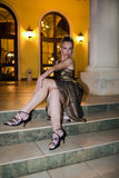 The woman in an evening dress sits on steps. At night Stock Image