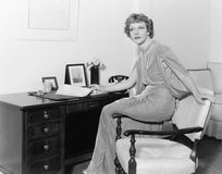 Woman in a evening dress sitting on the armrest of a chair stock image