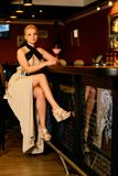 Woman in evening dress sitting near bar counter Stock Photo