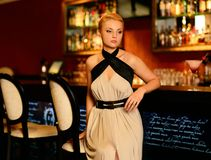 Woman in evening dress sitting near bar counter Royalty Free Stock Images