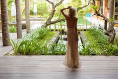 Woman in evening dress standing in exotic luxury tropical villa. Beautiful woman in evening dress standing in exotic luxury tropical villa royalty free stock images
