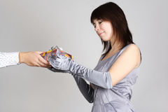 Woman in evening dress taking gift from mans hand Royalty Free Stock Image