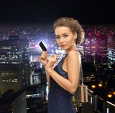 Woman in evening dress with vip card. Party, celebration, holiday and banking concept - beautiful woman in evening dress with small bag and vip card Stock Photos