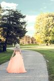 Woman in evening dress walking to manor house. Portrait of woman in evening dress walking to manor house Royalty Free Stock Photography