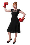 Woman in evening dress wearing boxing glove. Humorous concept of woman in evening dress wearing boxing glove, isolated on white Royalty Free Stock Photo