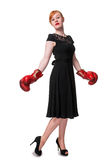 Woman in evening dress wearing boxing glove. Humorous concept of woman in evening dress wearing boxing glove, isolated on white Royalty Free Stock Photography