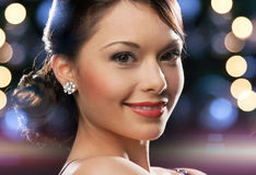 Woman in evening dress wearing diamond earrings. Luxury, vip, nightlife, party concept - beautiful woman in evening dress wearing diamond earrings Royalty Free Stock Photos