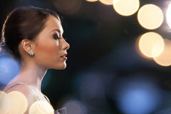 Woman in evening dress wearing diamond earrings Royalty Free Stock Image