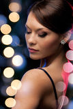Woman in evening dress wearing diamond earrings Stock Photos