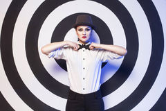 Woman with evening make up and red lips in a bow-tie in a center of a dartboard background Royalty Free Stock Photo