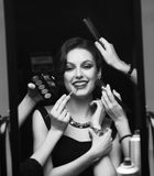 Woman with evening make up surrounded by the different brushes for make up Royalty Free Stock Image