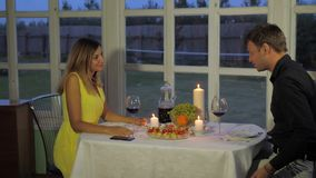 Woman Evening Sitting At The Table, A Man Comes, They Kiss And Drink Red Wine. Beautiful woman in a yellow dress sits in the evening at a restaurant at a table stock video footage