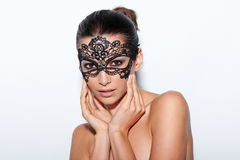 Woman with evening smokey makeup and black lace mask. Closeup portrait of beautiful woman with evening smokey makeup and black lace mask over her eyes Stock Photos