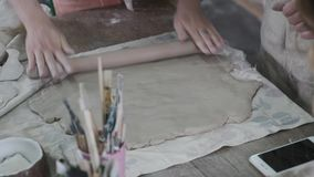 A woman evens the clay. With a tool stock footage