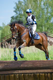 Woman eventer on horse is Drop fence in Water jump Stock Image