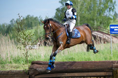 Woman eventer on horse is Drop fence in Water jump Royalty Free Stock Photo