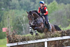 Woman eventer on horse is overcomes the fence Stock Photos