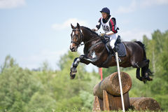 Woman eventer on horse is overcomes the Log fence Royalty Free Stock Photo