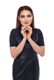 Woman with evil plans. Beautiful slim model with her hands near the face, gesture of confidence and evilness,  isolated against white background Stock Photo