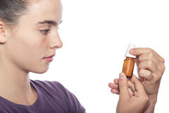 Woman is examine a bottle of homeopathic medicine Stock Images