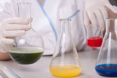 Woman examine colorful bottles fill with chemicals Stock Images