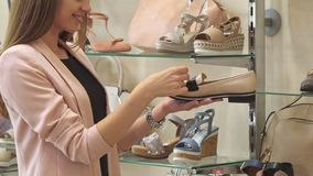 Woman examines beige shoe at the shop royalty free stock images
