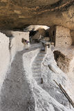 A Woman Examines Cave 4 at the Gila Cliff Dwellings Stock Image