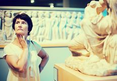 Woman examines the exhibit in historical museum. Mature woman examines the exhibit in historical museum royalty free stock photo