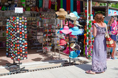 Woman examines goods in shop on waterfront in resort town of Petrovac, Montenegro Stock Images