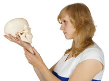 Woman examines a human skull on white Royalty Free Stock Images