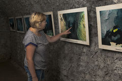 Woman examines a photo exhibition in one of dark halls Caves Bear Safari Park in Gelendzhik, Krasnodar region, Russia Royalty Free Stock Images