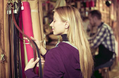 Woman examining belts in shop royalty free stock images