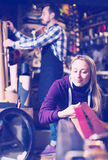 Woman examining belts in shop Stock Photography