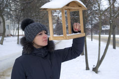 Woman examining a birdhouse in city park Royalty Free Stock Images