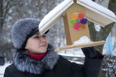 Woman examining a birdhouse in city park Stock Photo