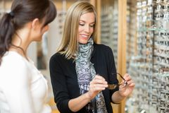 Woman Examining Eyeglasses With Salesgirl. Young women examining eyeglasses with salesgirl in optician store Royalty Free Stock Photo