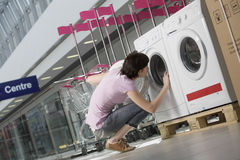 Woman Examining Front Loader Of Washing Machine. Full length of young women examining front loader of washing machine in shopping centre Royalty Free Stock Images