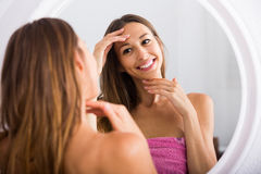 Woman examining her face by looking at it in mirror royalty free stock photo