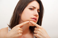 Woman examining herpes in her face Stock Photography
