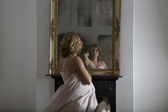 Woman Examining Herself In Mirror Royalty Free Stock Images