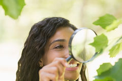 Woman examining leaves with magnifying glass Royalty Free Stock Images