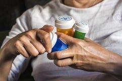 Woman examining medication treatment, several boats in the hand, conceptual image royalty free stock photos