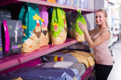Woman examining pet food. Smiling woman examining packs with pet food in pet shop stock images
