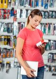 Woman Examining Product In Hardware Store Royalty Free Stock Photography