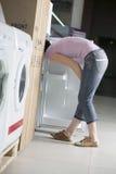 Woman Examining Refrigerator In Shopping Centre Stock Photo