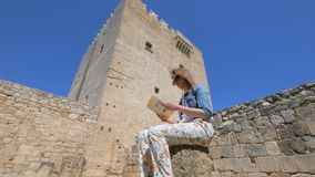 Woman is examining touristique brochure sitting near Kolossi castle in Cyprus. Tilt up shot stock footage