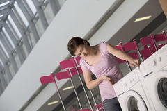 Woman Examining Washing Machine In Shopping Centre stock photos