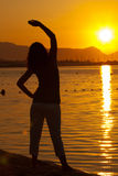 Woman excercising Yoga during sunset Stock Photos