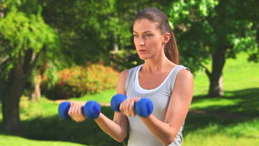 Woman excersising with dumbbells outdoors Royalty Free Stock Photos