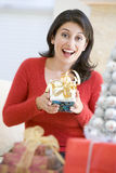 Woman Excited To Open Christmas Present Stock Photo